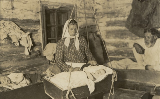 Fotografia z wnętrza chałupy: kobieta przy wiszącej kołysce