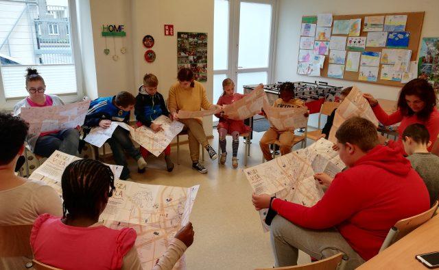 grupa młodzieży siedzi w kręgu na krzesłach i ogląda mapy Nasza Wola