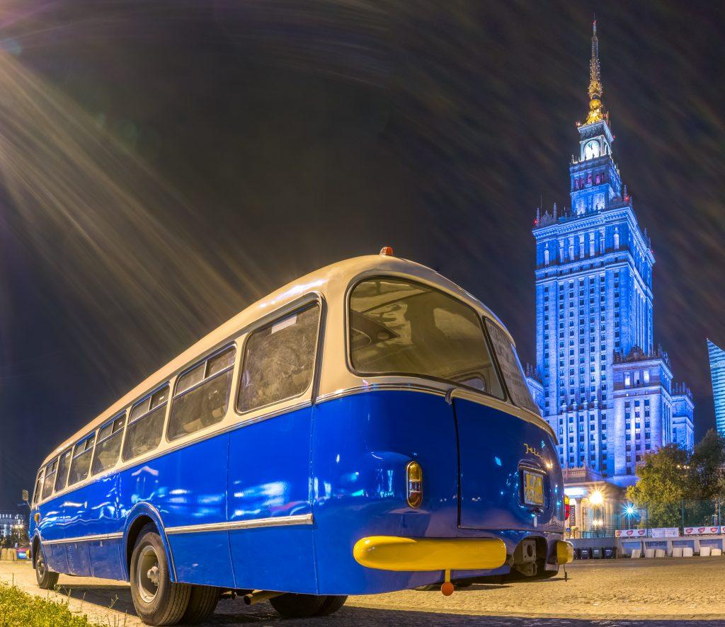 zdjęcie przedstawia biało-niebieski autobus ogórek natle podświetlonego naniebiesko Pałacu Kultury iNauki