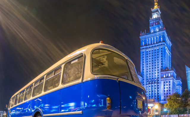 zdjęcie przedstawia biało-niebieski autobus ogórek na tle podświetlonego na niebiesko Pałacu Kultury i Nauki