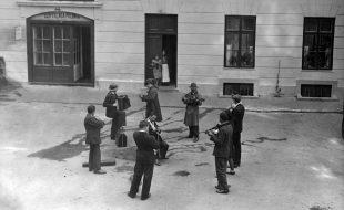 """czarno-biała fotografia, grupa muzyków występuje na ulicy, w tle kamienice, po lewej widoczny szyld nad wejściem: """"Czytelnia Polonia"""""""
